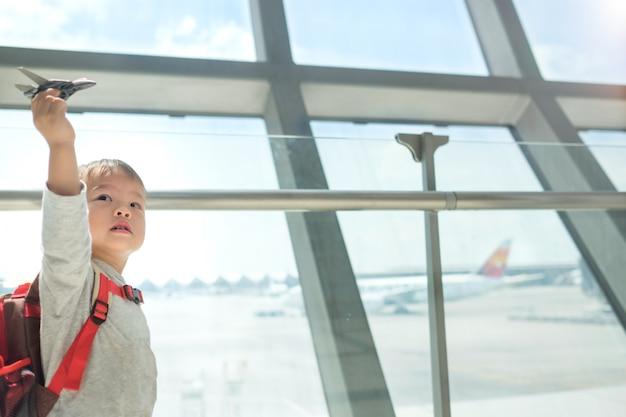Viajante pequeno, criança asiática se divertindo brincando com o avião Foto Premium