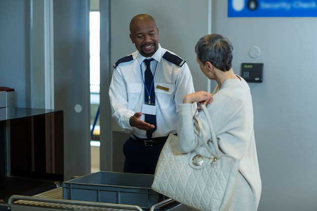 Viajante recebendo uma mala despachada do oficial de segurança do aeroporto Foto gratuita