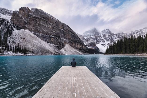 Viajante sentado no cais de madeira com montanha rochosa no lago moraine no parque nacional de banff Foto Premium
