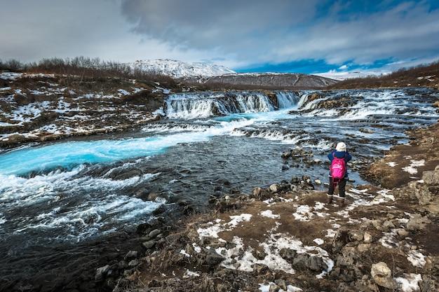 Viajante tirando foto da cachoeira de bruarfoss na temporada de inverno Foto Premium