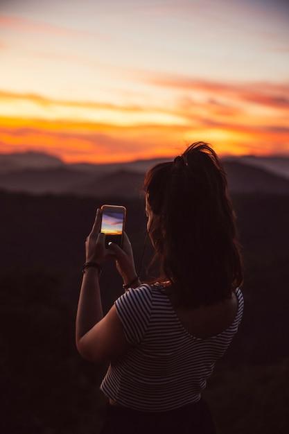 Viajante tirando uma fotografia do pôr do sol Foto gratuita