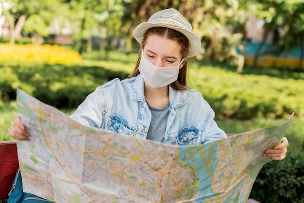 Viajante usando máscara médica, olhando para o mapa Foto gratuita