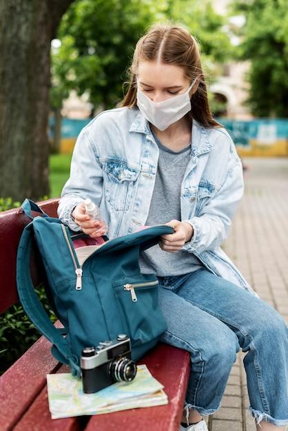 Viajante, usando máscara médica, tendo uma câmera retro Foto gratuita