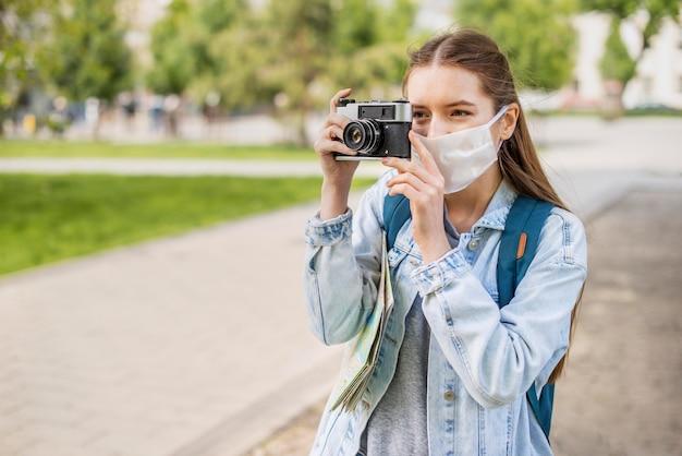 Viajante usando máscara médica tirando uma foto Foto gratuita