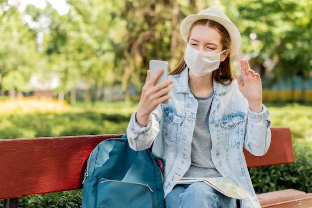 Viajante usando máscara médica usando seu telefone Foto Premium
