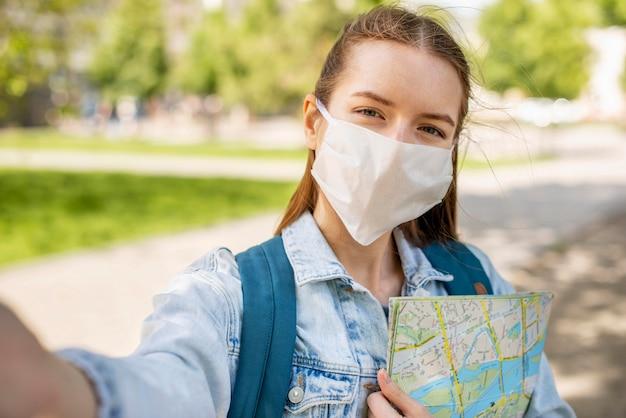 Viajante vestindo máscara médica e selfie de mapa Foto Premium