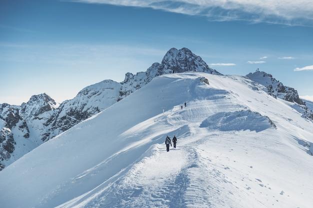 Viajantes alpinista vai ao pico nevado em montanhas. Foto Premium