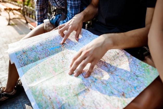 Viajantes de amigos sorrindo, olhando a rota no mapa, sentado no banco. Foto gratuita