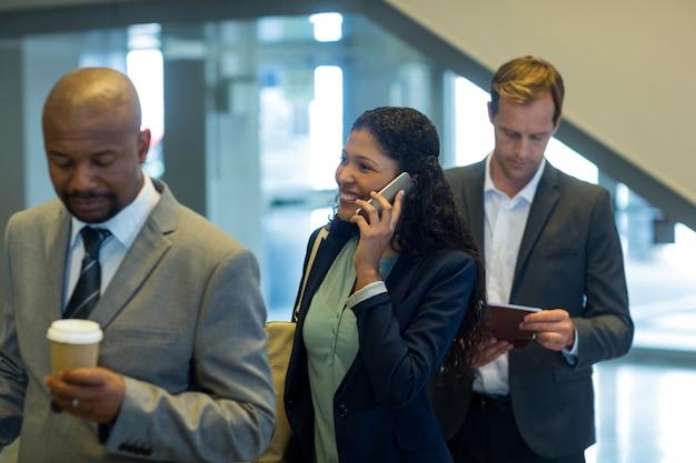 Viajantes de negócios esperando na fila Foto gratuita