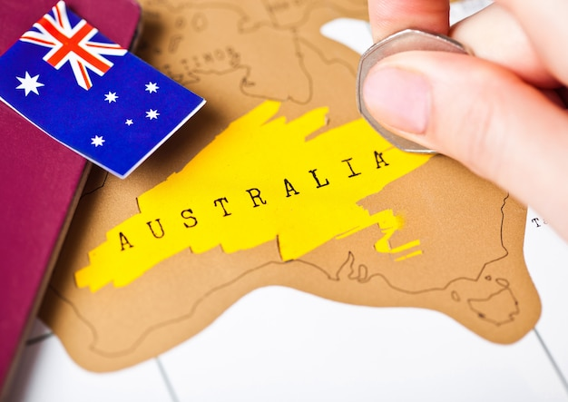 Viajar de férias para o conceito de austrália com passaporte e bandeira com mão feminina, escolhendo a austrália no mapa Foto Premium