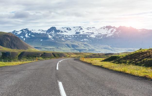 Viajar para a islândia. estrada em uma paisagem de montanha ensolarada brilhante. vulcão vatna coberto de neve e gelo na tne Foto Premium
