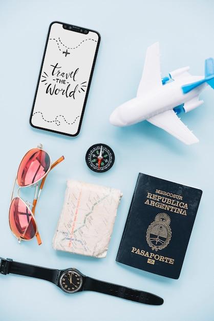 Viaje a mensagem do mundo no smartphone com óculos de sol; relógio de pulso; mapa; passaporte; bússola e avião de brinquedo Foto gratuita