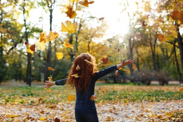 Vibrações de outono, retrato de criança. cabelo encantador e vermelho menina parece feliz andando e jogando em t Foto gratuita