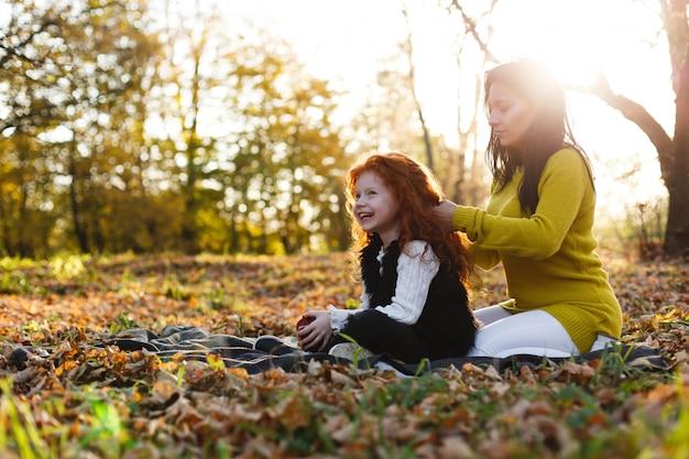 Vibrações de outono, retrato de família. mãe encantadora e sua filha de cabelo vermelho se divertir sentado sobre o caído Foto gratuita