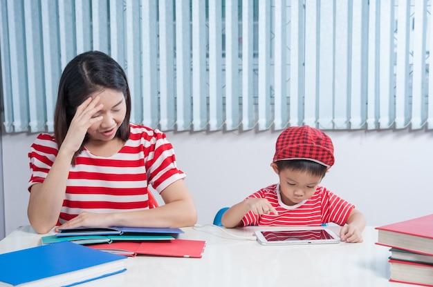 Vício em informática. boy playing tablet e sua mãe frustrada. Foto gratuita