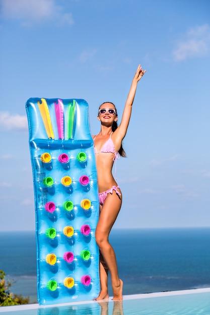Vida de luxo, retrato de verão de estilo de férias de mulher jovem feliz com corpo magro bronzeado, tendo sol na villa de luxo, segurando colchões de ar nas mãos dela. Foto gratuita