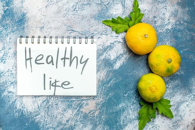 Vida saudável de mandarinas frescas de vista superior escrita no bloco de notas na superfície branca Foto gratuita