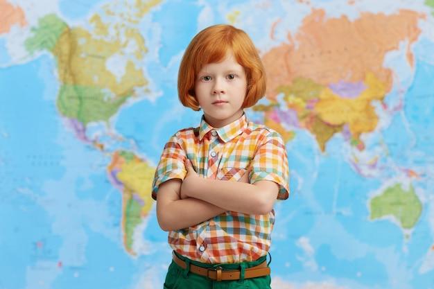 Vidente menino pequeno com cabelos ruivos, mantendo as mãos cruzadas em pé contra o mapa, vindo para o professor de geografia. clver garoto vai para a primeira classe, tendo um olhar confiante Foto gratuita