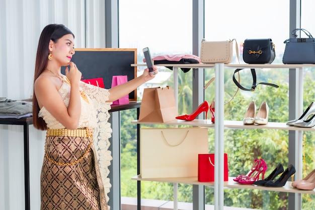 Vídeo chamada de mulher bonita com telefone em traje tradicional nacional da tailândia na loja shpping. Foto Premium
