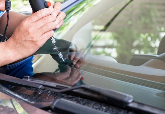 Vidraceiro usando ferramentas de reparação para consertar crack Foto Premium