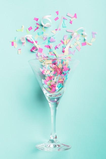 Vidro com confete no fundo turquesa Foto gratuita