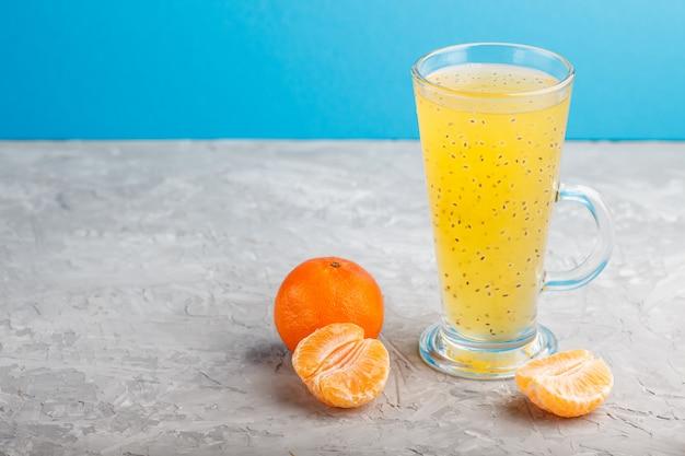 Vidro da bebida colorida laranja da tangerina com sementes da manjericão em uma superfície cinzenta. vista lateral Foto Premium