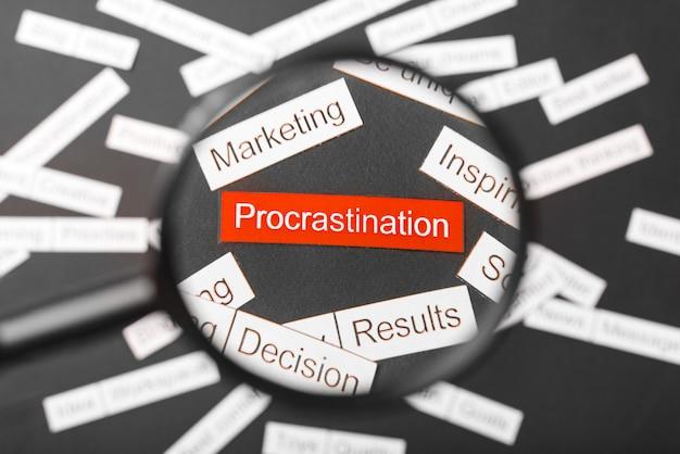 Vidro da lupa sobre a procrastinação vermelha inscrição recortada em papel. cercado por outras inscrições em um escuro. palavra nuvem . Foto Premium