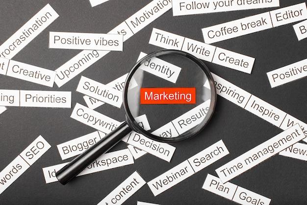 Vidro da lupa sobre o marketing vermelho inscrição recortado em papel. rodeado por outras inscrições Foto Premium