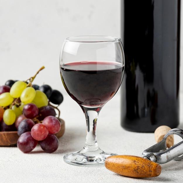 Vidro de alto ângulo com vinho tinto ao lado de uvas Foto Premium