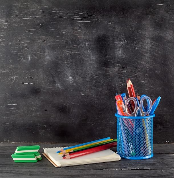 Vidro de papelaria azul com lápis e canetas de madeira multicoloridas Foto Premium