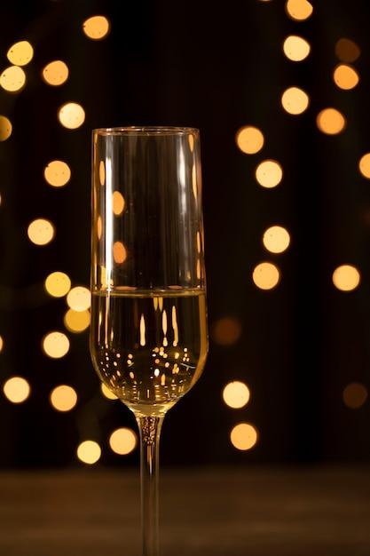Vidro de vista frontal com champanhe na festa de ano novo Foto gratuita
