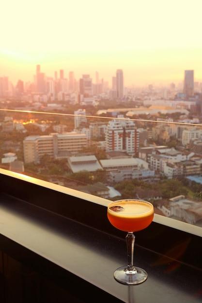 Vidro do cocktail na barra do telhado com vista urbana aérea no fundo. Foto Premium