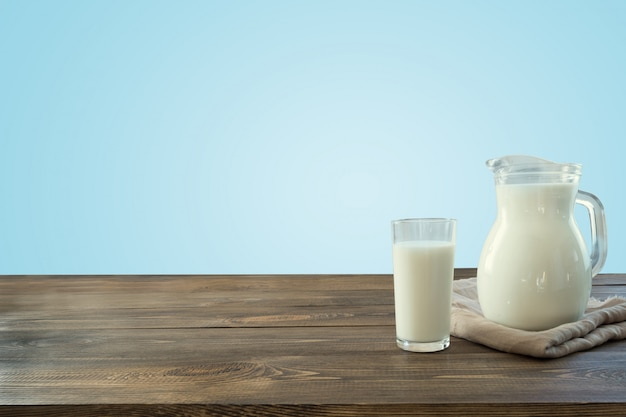 Vidro do leite e do jarro frescos no tabletop de madeira com a parede azul como o fundo. Foto Premium