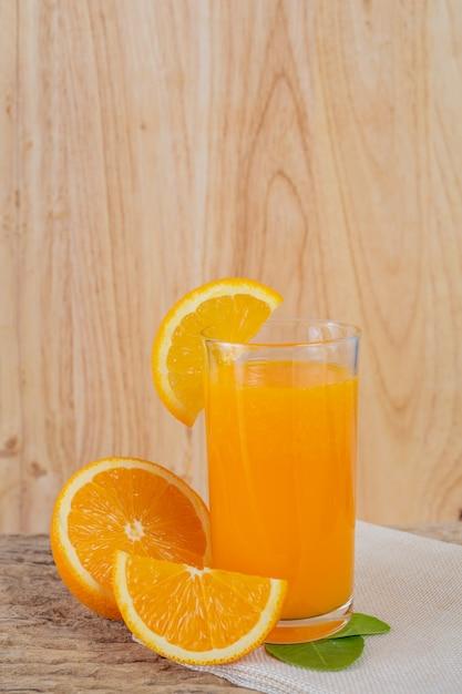 Vidro do sumo de laranja colocado na madeira. Foto gratuita