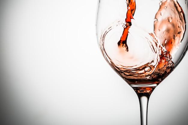 Vidro transparente na haste fina no fundo em branco com vinho Foto Premium