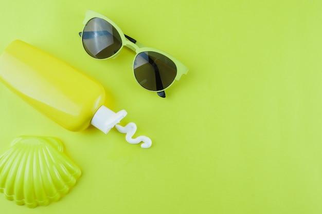 Vieira de plástico; loção protetor solar e óculos escuros sobre fundo verde Foto gratuita