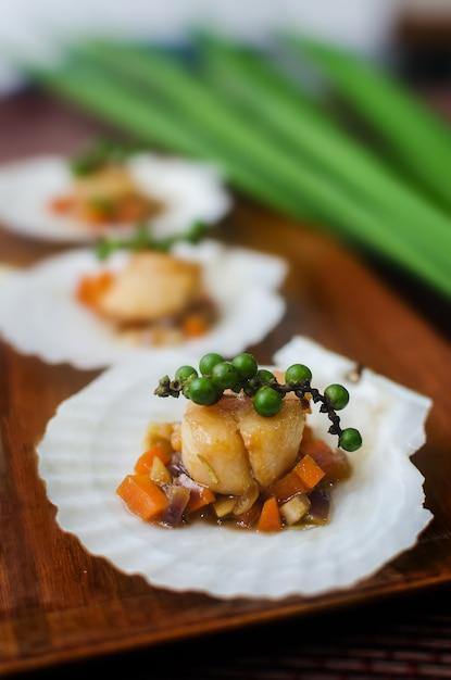 Vieiras com legumes em uma concha de vieira. Foto Premium