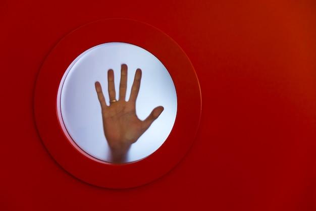 Vigia vermelha redonda com mão feminina. Foto Premium
