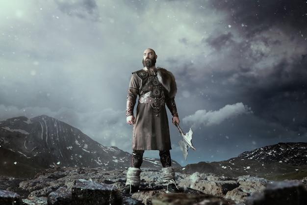 Viking com machado vestido com roupas nórdicas tradicionais, de pé nas montanhas rochosas. antigo guerreiro escandinavo Foto Premium