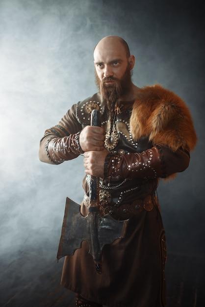 Viking com machado vestido com roupas tradicionais, imagem bárbara nórdica. guerreiro antigo em fumaça Foto Premium