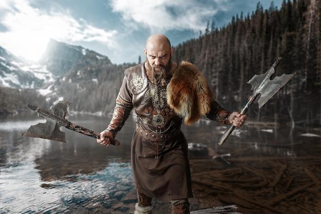 Viking com machados nas mãos, vestidos com roupas tradicionais nórdicas, em pé no lago. antigo guerreiro no rio, montanhas rochosas Foto Premium