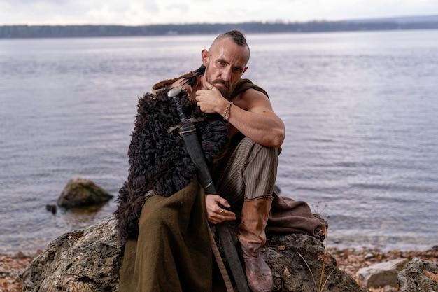 Viking é atencioso e senta-se em uma pedra segurando uma espada inserida em uma bainha Foto Premium