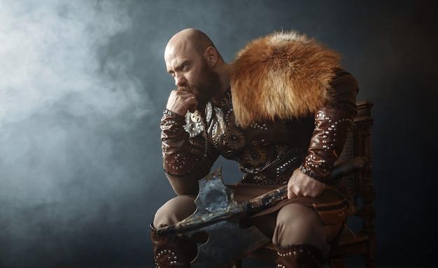 Viking pensativo com machado, vestido com roupas tradicionais nórdicas, sentado na cadeira, imagem de bárbaro. guerreiro antigo em fumaça Foto Premium