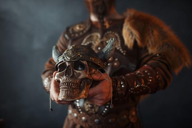 Viking segurando crânio humano em capacete Foto Premium