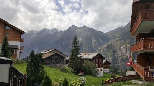 Vila suíça típica com as casas de madeira sobre o declive das montanhas alpinas ásperas. Foto Premium
