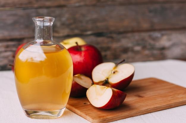 Vinagre orgânico de maçã em uma jarra de vidro com maçãs maduras frescas de vermelhas e amarelas em fundo de madeira. Foto Premium