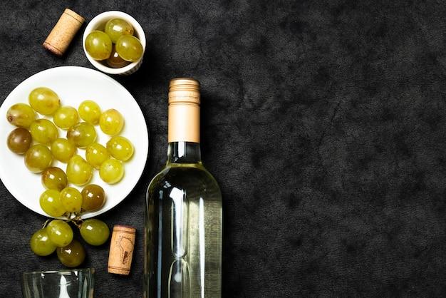 Vinho branco de vista superior com uvas Foto gratuita