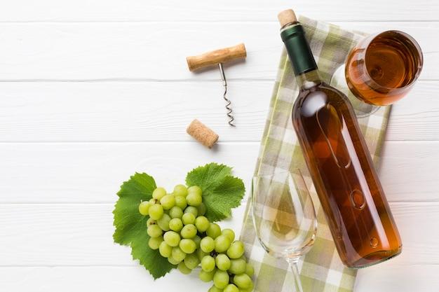 Vinho branco e copos em fundo de madeira Foto gratuita