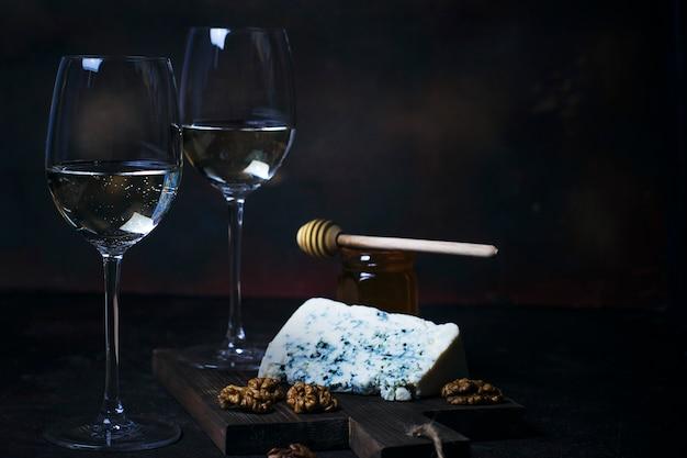 Vinho branco em copo fino com queijo azul, mel, nozes no escuro Foto gratuita