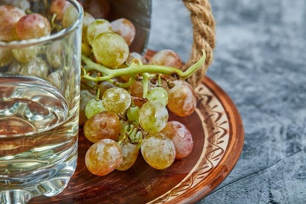 Vinho branco em um copo com um cacho de uvas verdes ao redor. Foto gratuita